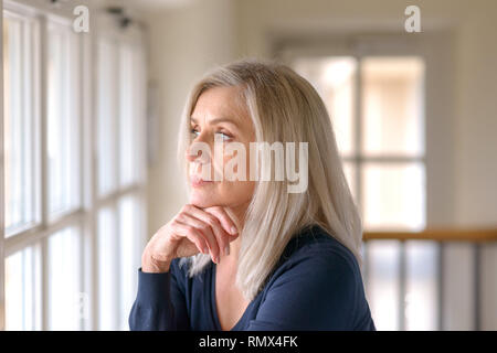 Attractive thoughtful woman with serious expression standing with her hand to her chin staring quietly out of a large window - Stock Photo