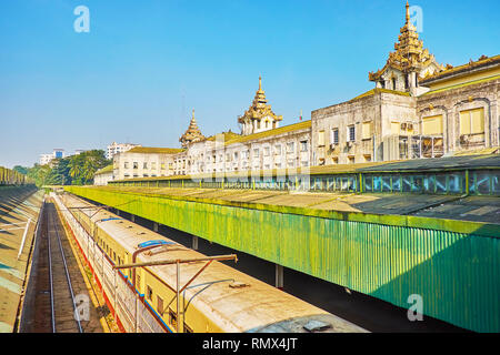 The old train arrives to the terminal of Yangon central railway station, its main building is seen on the background, Myanmar. - Stock Photo
