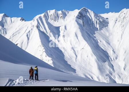 Two skiers standing on top of freeride zone in Gudauri mountains, Georgia - Stock Photo
