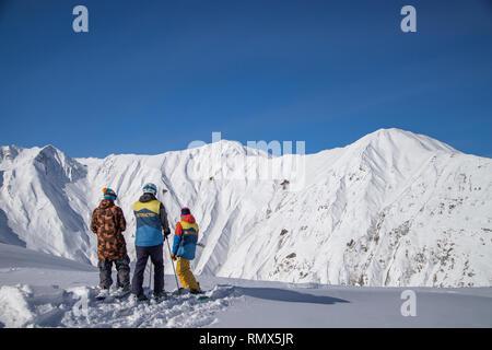 Three skiers standing on top of freeride zone in Gudauri mountains, Georgia - Stock Photo