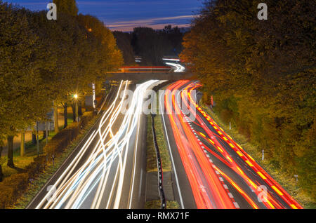 Long exposure light trails of traffic on a freeway in evening light driving through wooded countryside viewed from a high angle on a bridge - Stock Photo