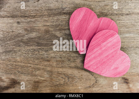 wooden heart love symbol pink paint on wood table with copy space. - Stock Photo