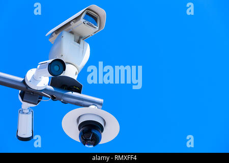 Few closed-circuit television cameras mounted on one pole under blue sky - Stock Photo
