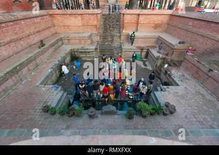 PATAN SQUARE, KATHMANDU, NEPAL-CIRCA 2013 : Unidentified Nepalese collect fresh water at a nearby temple in Patan Square, Kathmandu, Nepal. - Stock Photo