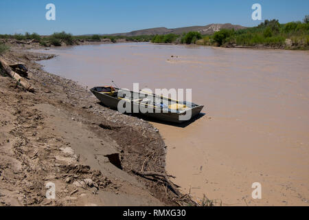 A small boat, skiff, waits on the United States side of the Rio Grande across from Boquillas del Carmen, Mexico. - Stock Photo