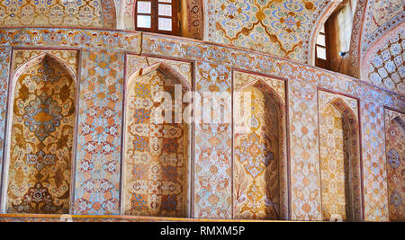 ISFAHAN, IRAN - OCTOBER 21, 2017: The wall with ornate arched niches in Reception hall of medieval Ali Qapu Palace, famous for its unique naturalistic - Stock Photo