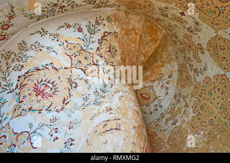 ISFAHAN, IRAN - OCTOBER 21, 2017: The walls and ceiling in staircase corridor of Ali Qapu palace are covered with preserved Persian floral patterns in - Stock Photo
