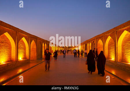 ISFAHAN, IRAN - OCTOBER 21, 2017: Walk along the evening pedestrian Siosepol (Allahverdi Khan) bridge with illuminated brick niches on both sides, on  - Stock Photo