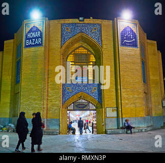 ISFAHAN, IRAN - OCTOBER 21, 2017: The evening illumination of the entrance portal (iwan) of Honar Bazaar with fine tile patterns and inscriptions, on  - Stock Photo