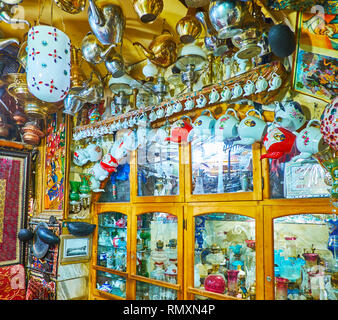 ISFAHAN, IRAN - OCTOBER 21, 2017: The glass door buffet with kerosene lamps and many vintage teapots, hanging on wall and ceiling of Azadegan Chaykhun - Stock Photo