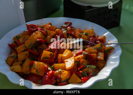 The originally roasted pink tasty pieces of grilled vegetables in a white plate on the background of the table. The concept of delicious and healthy f - Stock Photo