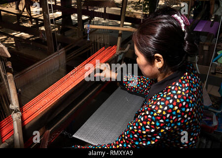 Cambodia, Phnom Penh, Koh Dach, Silk Island traditional weaving centre, woman weaving patterned cloth - Stock Photo