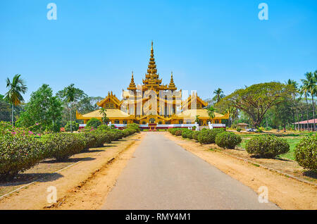 The alley of the ornamental garden leads to historic Kanbawzathadi palace, richly decorated in traditional Burmese style, Bago, Myanmar. - Stock Photo