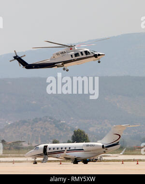A Sikorsky s-76c Spirit with tail no. TC-HKA lands next to an Embraer emb 550 legacy 500 business jet with tail no. OD-CXJ. - Stock Photo