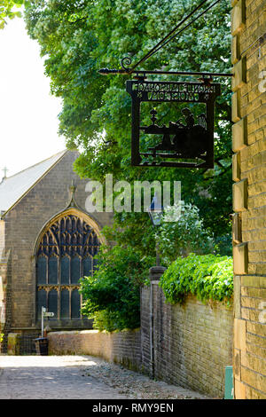 Close-up of black metalwork sign hanging on exterior wall of Bronte Parsonage Museum (Brontes home) & church beyond - Haworth, Yorkshire, England, UK. - Stock Photo