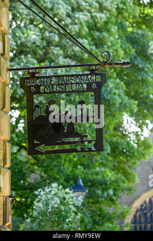 Close-up of black metalwork sign (cut out design) hanging high on exterior wall of Bronte Parsonage Museum - Haworth, West Yorkshire, England, UK. - Stock Photo