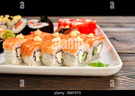 Close up of delicious philly rolls, covered with salmon and decorated with mayo. Sushi set of different kinds of uramaki and maki rolls, served on white plate. - Stock Photo