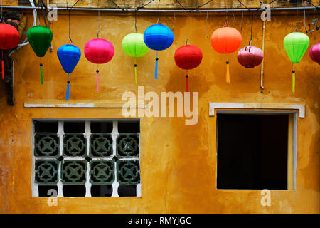 Old windows in the historic UNESCO listed central Vietnamese town of Hoi An, where yellow walls are traditional - Stock Photo