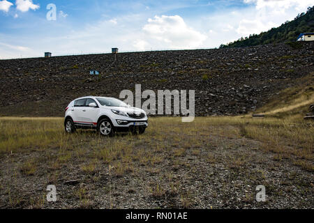 car Kia Sportage 2.0 CRDI awd or 4x4, white color, on the meadow. - Stock Photo