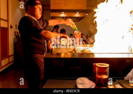 Riviera Maya, Mexico - July 28, 2018. Japaneses Tepanyaki chef entertains diners in a luxury restaurant with an exciting show of flames on a hot shove - Stock Photo