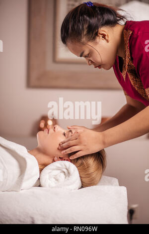 Chinese guy massaging the woman's temples. close up side view photo. leisure. - Stock Photo