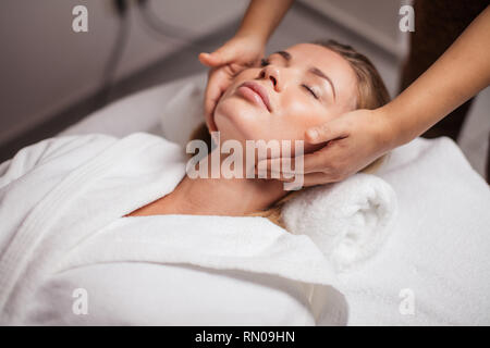 girl takes care of her face. massage which makes you feel and look younger. - Stock Photo