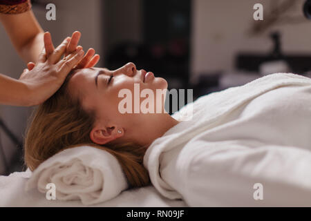 reset tired body. girl enjoys professional massage. close up side view photo. soothing the muscles - Stock Photo