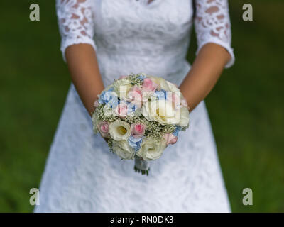 Beautiful tender wedding bouquet of cream roses and eustoma flowers in hands of the bride. - Stock Photo