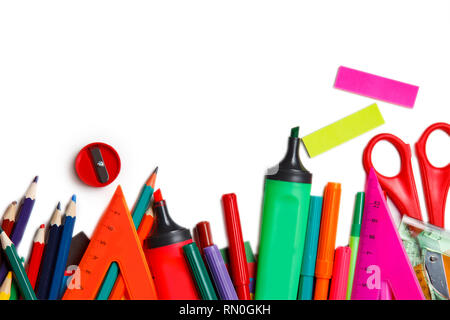 Assorted school supplies, including pens, pencils, scissors, glue and a ruler, on a white background - Stock Photo