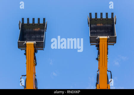 Construction business industry two new excavators machines together outdoors with steel arms extended and bucket scoops closeup into blue sky. - Stock Photo
