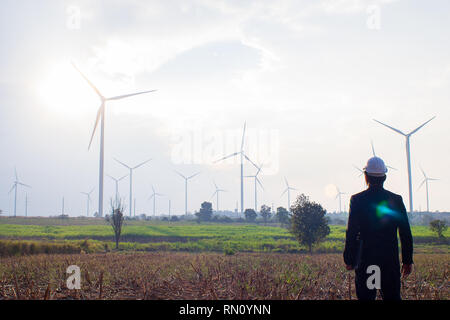 Engineer standing and playing laptop with wind turbine. - Stock Photo