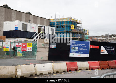 New project funded by the council to build Carmarthenshire Archives building in St Peters Car Park. Builder stood outside site office. - Stock Photo