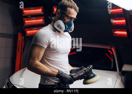 serios man turning on an electric polishing device during work. close up photo. - Stock Photo