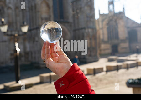 Woman holding a glass ball in her hand in front of York Minster,North Yorkshire,England,UK. - Stock Photo