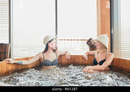 Two relaxing girl spend their day off in luxury spa centre, sharing ideas and news while taking a whirlpool bubble bath - Stock Photo