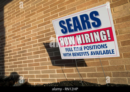 A 'Now Hiring' sign outside of a Sears retail store location in Harrisburg, Pennsylvania on February 9, 2019. - Stock Photo