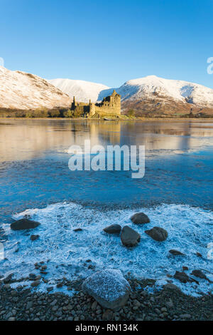 Early morning at Kilchurn Castle and Loch Awe, Argyll and Bute, Scotland, UK on a cold winters day with snow and frozen loch