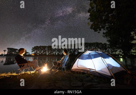 Night camping on lake shore. Man and woman friends sitting on chairs near campfire and illuminated tent, enjoying incredible view of evening sky full of stars and Milky way, city lights on background. - Stock Photo