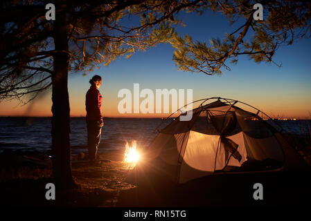 Night camping at sea coast under clear blue sky. Attractive tourist woman having a rest alone at campfire near tent on clear water and distant lights on horizon background. Tourism and recreation. - Stock Photo