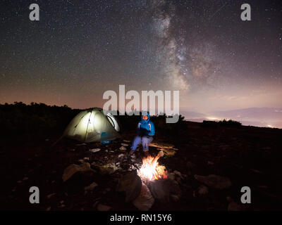 Female camper having a rest at summer night camping in the mountains beside bonfire and illuminated tourist tent. Young woman backpacker enjoying view of night sky full of stars and Milky way. - Stock Photo