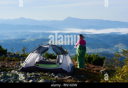 Camping on the top of mountain on bright summer morning. Happy hiker woman in pink sweater and sleeping bag having a rest beside tourist tent. On foggy mountains background. Tourism adventure concept - Stock Photo