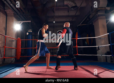 Young fighter practicing kickboxing with his trainer in the ring at the health club - Stock Photo