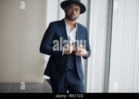elegance. stylish guy in hat is touching his jacket. close up photo. - Stock Photo