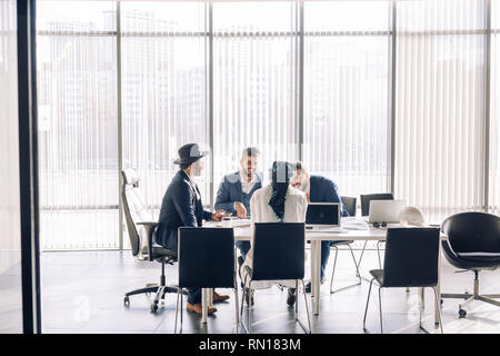 Elegant well-dressed business men of different age and ethnicity in suits gathered together for negotiating, collaborating in spacious modern office m - Stock Photo