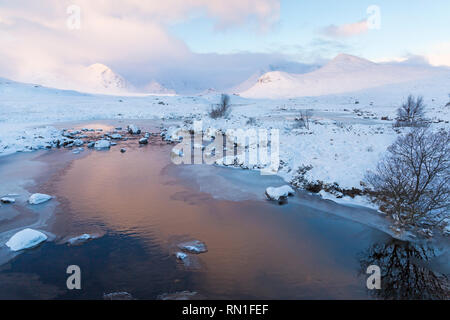 Cold winter morning with partially frozen loch and sunrise reflected in water at Loch Ba, Rannoch Moor, Argyll and Bute, Scotland in January - Stock Photo