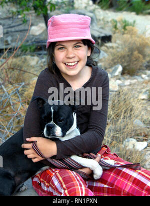 Sweet young girl cuddles her dog and smiles.  She is happy and showing her pet affection.  She has on a pink hat. - Stock Photo
