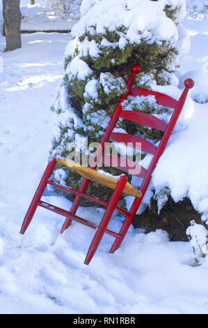 Someone left Grandpa's chair out in the cold.  Chair is wooden, red and leans against a cedar tree out in the snow. - Stock Photo