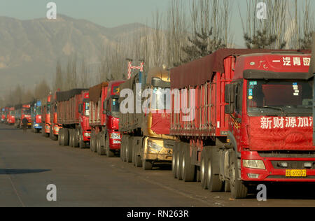 Datong, Shanxi, China. 12th Dec, 2018. Coal trucks parked outside a mine wait for the green-light to pickup a load of coal in Datong, Shanxi Province (China's coal country), on December 12, 2018. China is the largest producer and consumer of coal in the world, making it the leading emitter of greenhouse gases from coal. China burns much more coal than reported, which has continued to complicate climate talks. Credit: Stephen Shaver/ZUMA Wire/Alamy Live News - Stock Photo