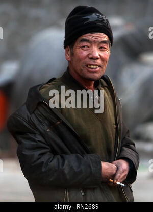 Datong, Shanxi, China. 12th Dec, 2018. A Chinese coal miner has a smoke while working near a tunnel in Datong, Shanxi Province (China's coal country), on December 12, 2018. China is the largest producer and consumer of coal in the world, making it the leading emitter of greenhouse gases from coal. China burns much more coal than reported, which has continued to complicate climate talks. Credit: Stephen Shaver/ZUMA Wire/Alamy Live News - Stock Photo
