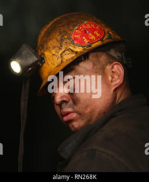 Datong, Shanxi, China. 12th Dec, 2018. A Chinese coal miner works near a tunnel in Datong, Shanxi Province (China's coal country), on December 12, 2018. China is the largest producer and consumer of coal in the world, making it the leading emitter of greenhouse gases from coal. China burns much more coal than reported, which has continued to complicate climate talks. Credit: Stephen Shaver/ZUMA Wire/Alamy Live News - Stock Photo